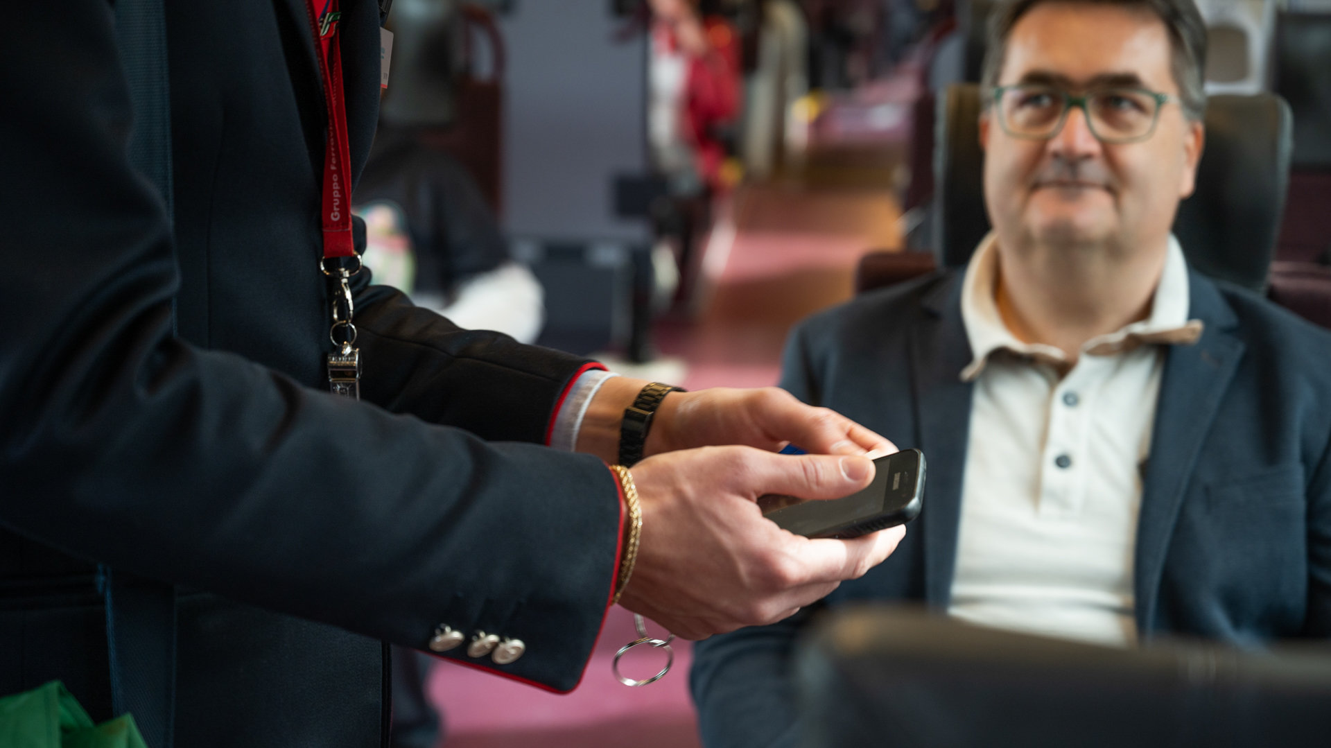 A ticket inspector checks a ticket using his smartphone.