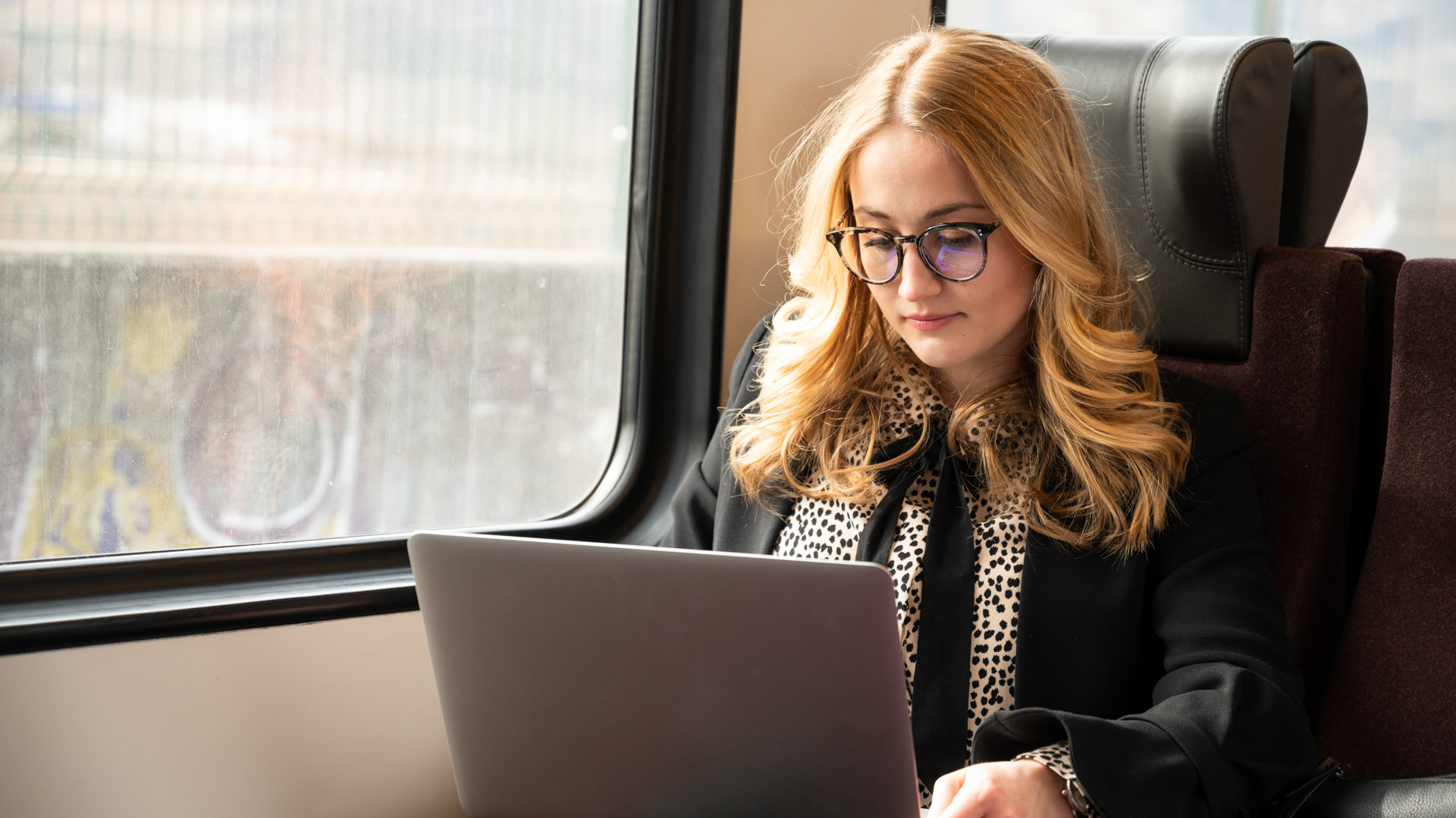 A girl with glasses working on her laptop on the train
